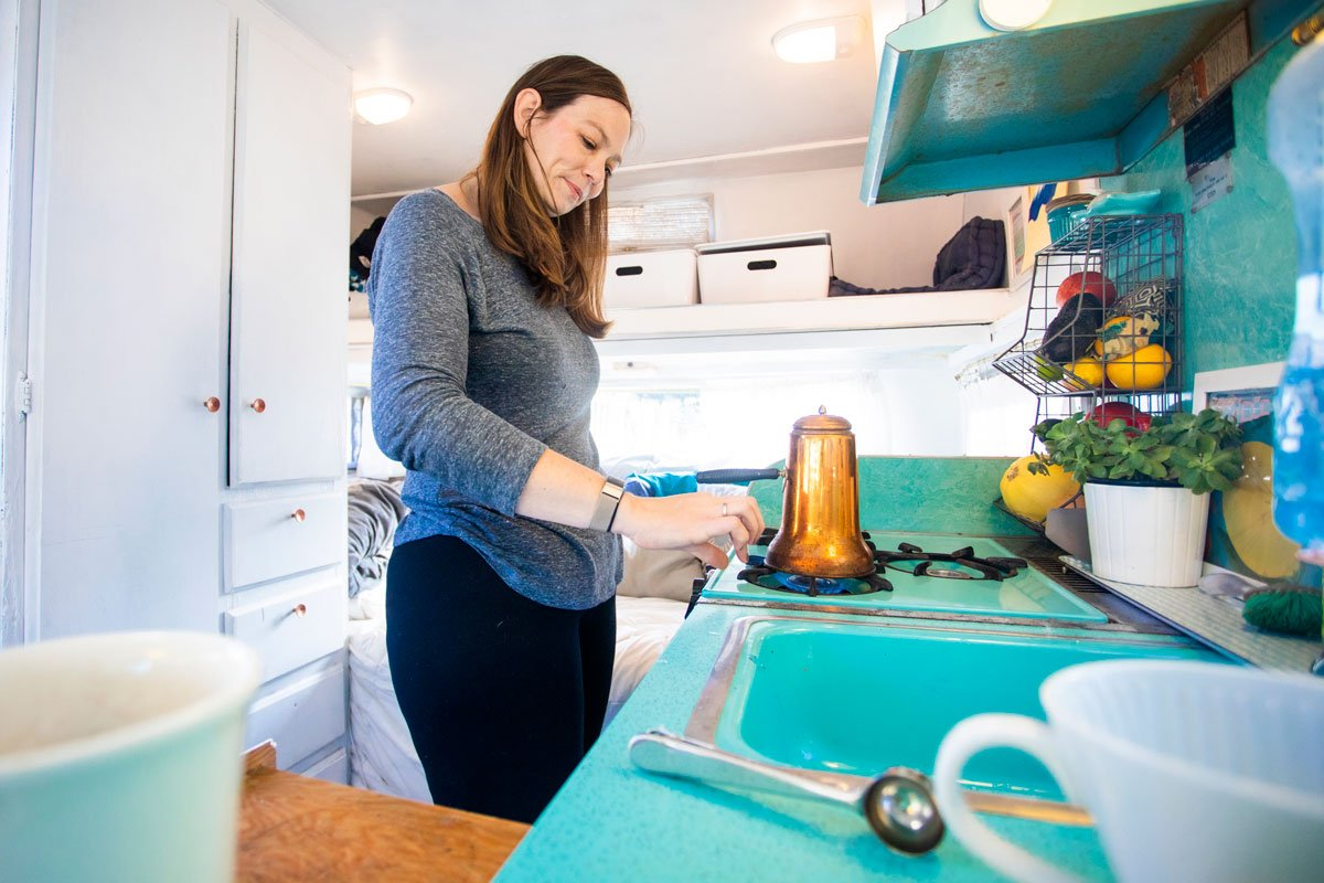 A woman makes coffee in her travel trailer.