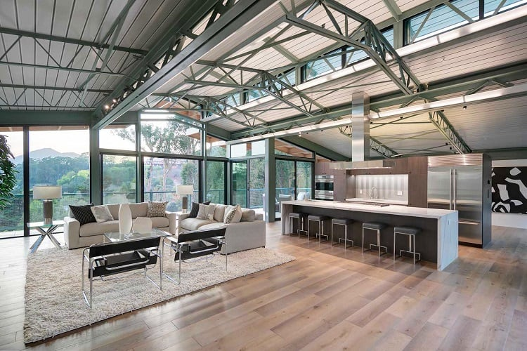The house boasts a modern industrial design with soaring steel beamed ceilings.