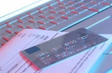 credt card sitting on bill on keyboard to show late credit card payment
