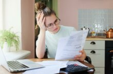 A young woman looks at health insurance paperwork with frustration and confusion